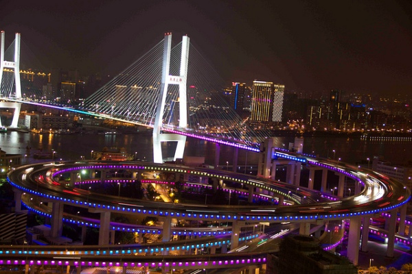 The Nanpu Bridge off ramp, illuminated at night. Photo by jijis [CC BY 2.0] via this flickr page