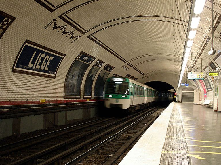 Liège station. Bands of brown tiling run across the ceiling, and station names and poster adverts are framed with brown tiles too. Not also the tiled swag patterns. By Clicsouris (Own work (Photo personnelle)) [CC-BY-SA-3.0], via Wikimedia Commons