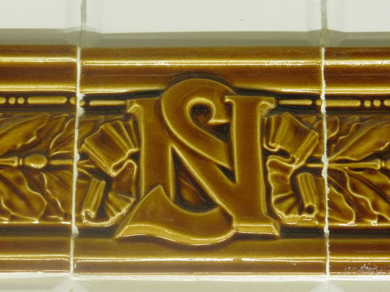 Nord-Sud monogram in the tiling surrounding a station name. By Tangopaso (Own work) [Public domain], via Wikimedia Commons