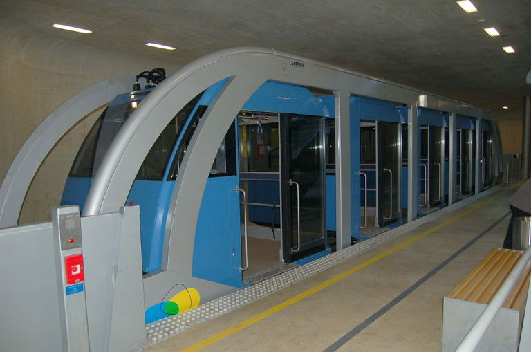 One of the Hungerburgbahn vehicles on level track at the underground station in Innsbruck. All the blue cabins are sitting in a line within the grey 'cage' which is what the wheels and cable are attached to. By Wolfgang Glock (Own work) [CC-BY-3.0], via Wikimedia Commons