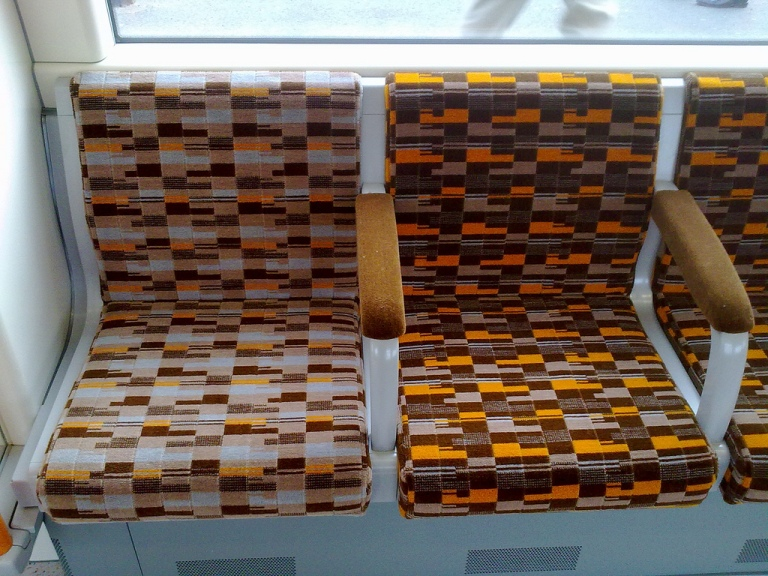Seats on a London Overground train. The priority seating moquette is on the left, the standard seating moquette is on the right. By mac morrison [CC BY-SA 2.0] via this flickr page