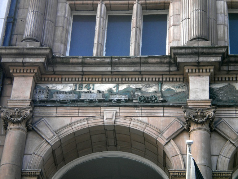 Detail of the frieze on the Thomas Cook Building, Leicester, UK. This shows the 1841 train that invented the charter train business. © Paul Wright (used with permission)