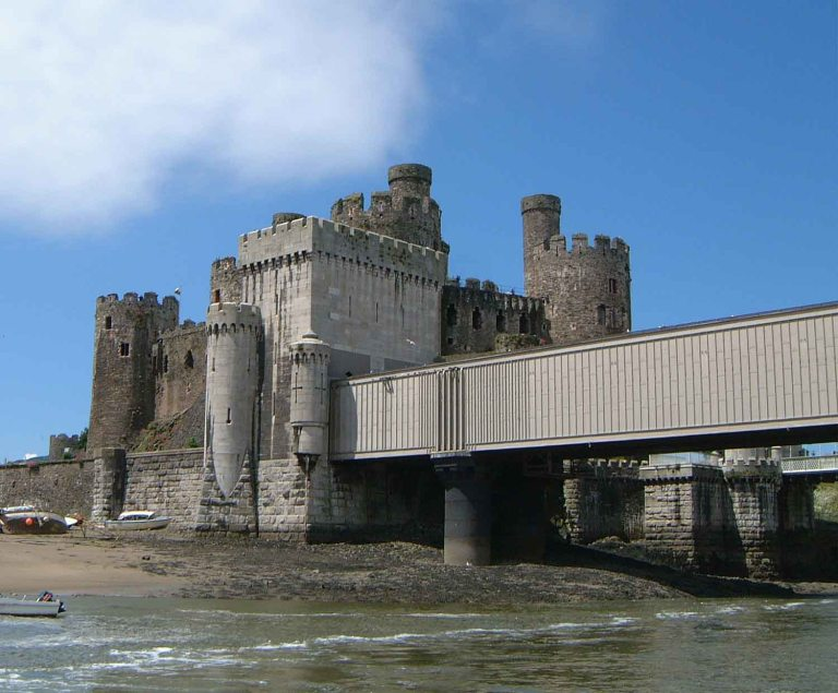 Stephenson's bridge, in front of Conwy Castle. The similarities and differences in design of the details of the two buildings are intriguing. By Mick Knapton at the English language Wikipedia [GFDL or CC-BY-SA-3.0], from Wikimedia Commons