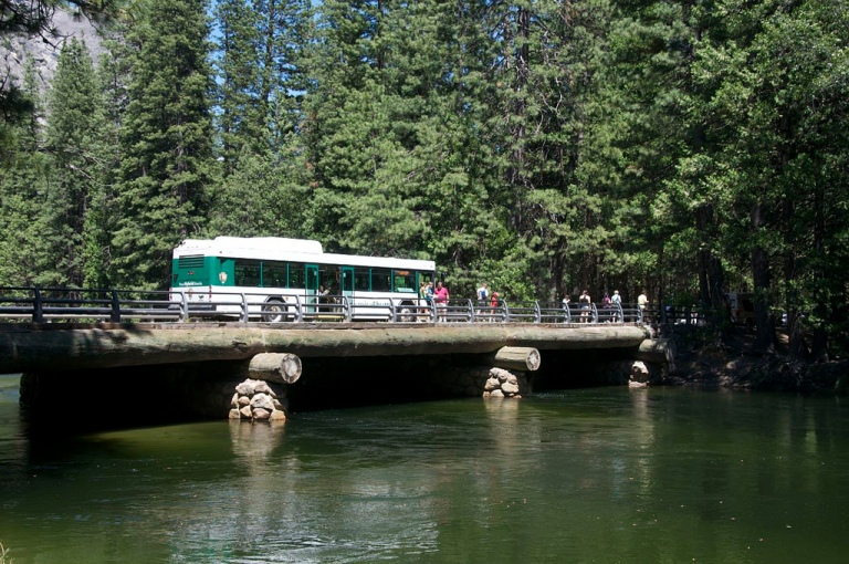 Yosemite National Park shuttle bus. Photo by Doug Barber [CC BY 2.0] via this flickr page. This is a slightly gratuitous picture of a bus, but I needed to break up the text a bit.  However, it's worth noting that the log construction of the bridge is similar to that of the roof on the Yosemite Falls bus shelter.