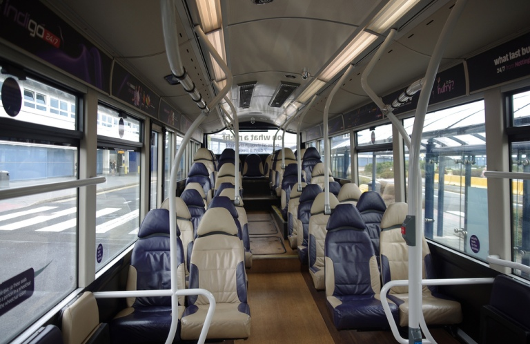 Interior of a trentbarton Indigo bus.  It's a regular city bus, but it has leather seats, air conditioning (even though train operators seem to think this is impossible for a public transport vehicle that makes frequent stops), and a very smart wood-effect floor. In other words, things you wouldn't dream of finding on most urban trains. Photo by