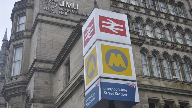 British Rail's double arrow, still on rail red, at the top of a totem sign outside Liverpool Lime Street station. Next is local transport authority Merseytravel's yellow M, and then Network Rail's station nameplate. Photo by David McKelvey [CC BY 2.0] via this flickr page
