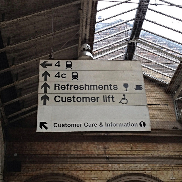 Rail Alphabet signage at Preston station. This is a typical BR scene, Rail Alphabet in black on a white background, distinctive directional arrows and pictograms, and everything (sign and building) a bit grimy. Photo by Jordan Hatch [CC BY 2.0] via this flickr page