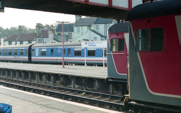 Network SouthEast's visual identity: trains in its red white and blue livery, signage with NSE chevron incorporated in a strip along the lower edge, and lampposts in red. This is Hastings station in 1991. Photo by Daniel Wright [CC BY-NC-ND 2.0] via this flickr page