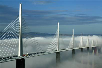 The Millau Viaduct with clouds below its bridge deck. Photo by Peter Stevens [CC BY 2.0] via this flickr page