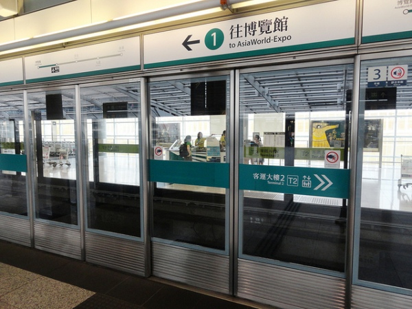 Signage at Hong Kong Airport station shows Airport Express's signature cool green line colour, and use of numbers for platforms (contrasting with letters for station exits). Photo by Fabio Achilli [CC BY 2.0] via this flickr page