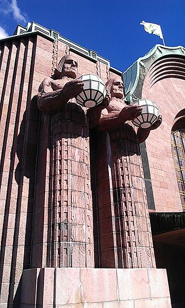 Two of the four statues flanking the main entrance at Helsinki Central. Ethan Doyle White at English Wikipedia [CC BY-SA 3.0], via Wikimedia Commons