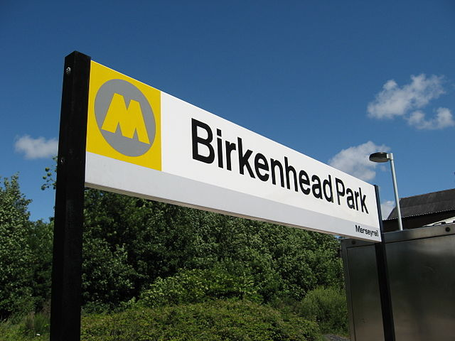 Merseytravel's logo, seen here on a sign at Birkenhead Park station. Photo by Redvers at English Wikipedia [CC BY 3.0], via Wikimedia Commons